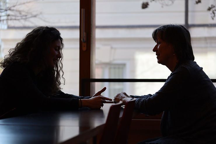 two people sitting at a table, facing each other as they talk