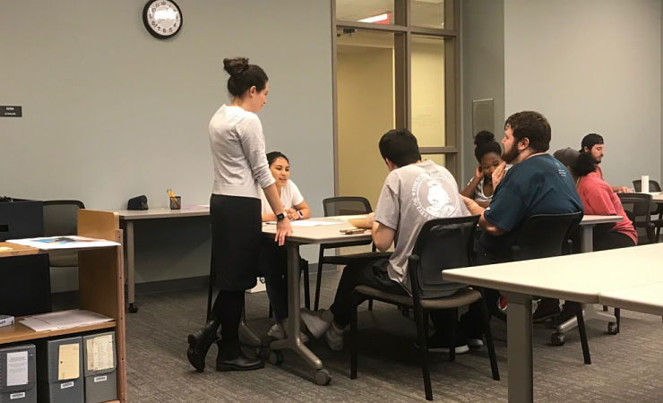 Margaret Ariotti standing before students at table