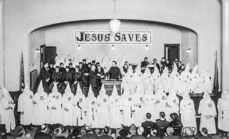 Hooded Ku Klux Klan members beneath Jesus Saves sign