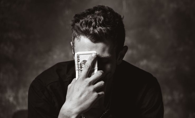 Distressed man holds stack on money to forehead