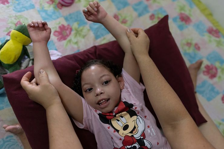 Mother holds up prone daughter's arms