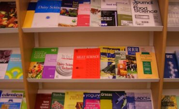 Library shelves with various journals lying flat