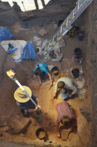 Archaeologists and students excavating the lowest reaches of the pit