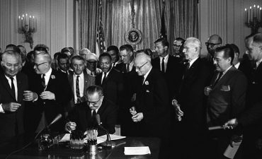 LBJ surrounded by men in suits as he signs bill